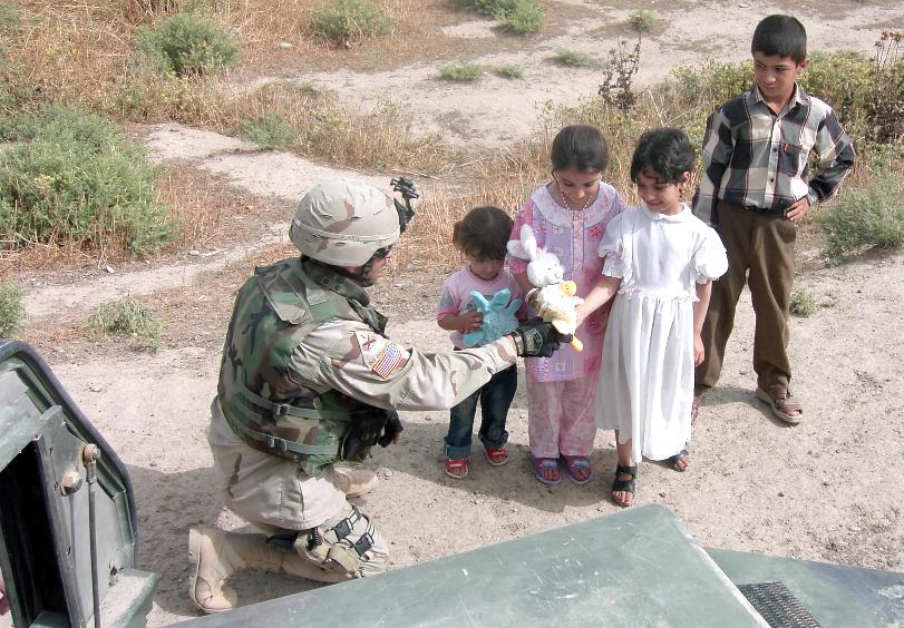 Photograph of an American soldier offering gifts to Iraqi children. Photograph by an American soldier of C Co, 1/252 Army Reserve Battalion.