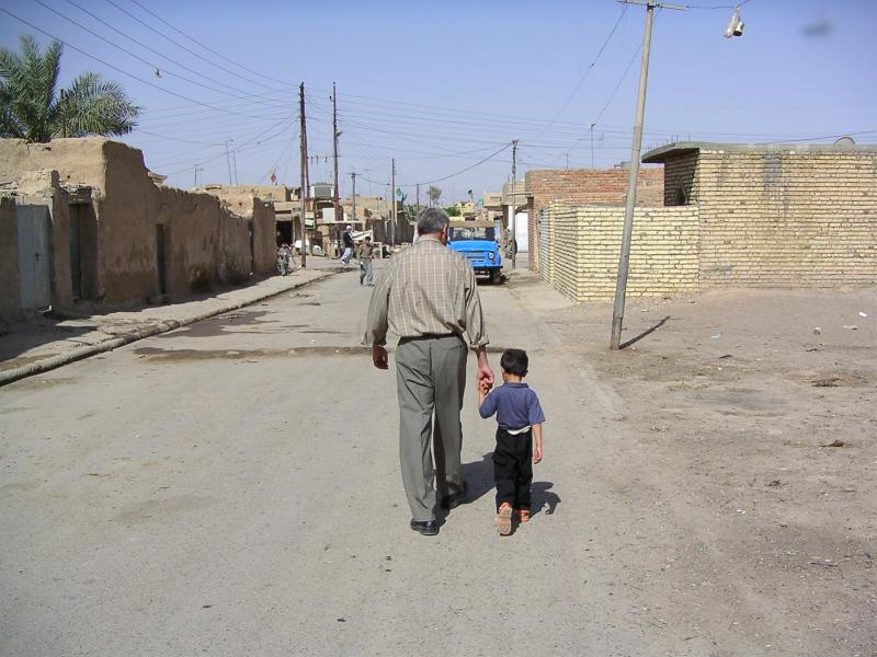 Photograph of a man holding the hand of a child, walking away down a street somewhere in Iraq. Photograph by an American soldier of C Co, 1/252 Army Reserve Battalion.